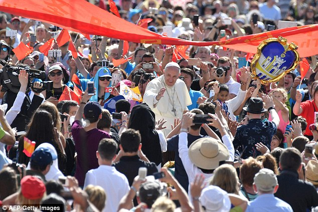 Pope Francis greets the crowd as he arrives for his weekly general audience