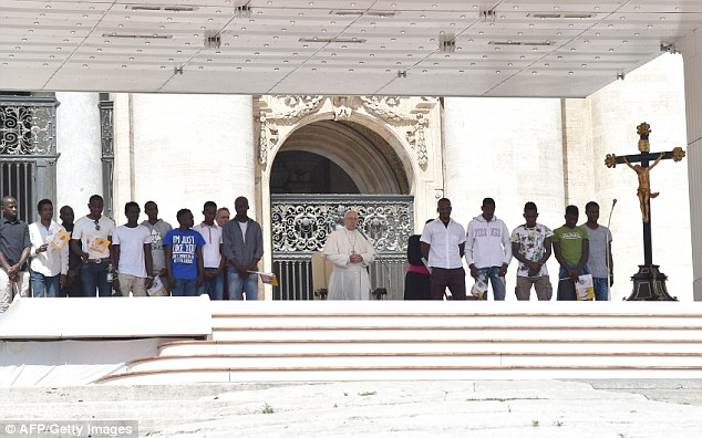 Pope Francis addresses the crowd surrounded by a group of refugees attending his weekly general audience at St Peter's square on June 22