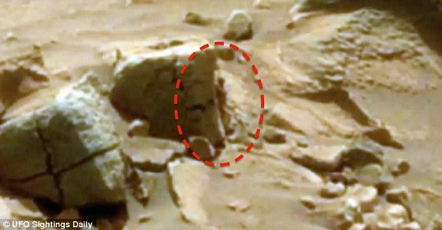 Apenas os pés de distância do rover Curiosity da NASA, o usuário Youtube Paranormal Crucible reivindica um pequeno alienígena humanóide pode ser visto espiando por trás de uma rocha marciana