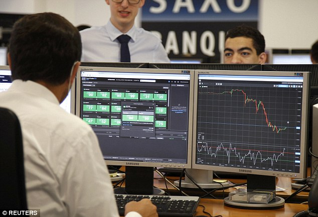 Cash crash: The FTSE opened 8 per cent down today as traders ran in fright from the shock Brexit result. Above, a trader sits in front of his screens, one which displays the rate of the British pound which drops against the US dollar