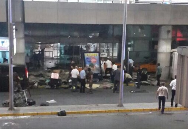 A photograph of the entrance to the international airport shows scattered debris as onlookers gather around to help the wounded - initially estimated to number around 40 people