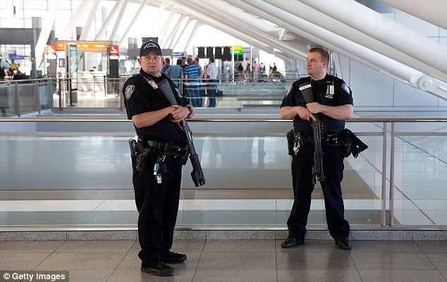 Vigilance: Port Authority police officers stand guard near a departures entrance at John F. Kennedy International Airport