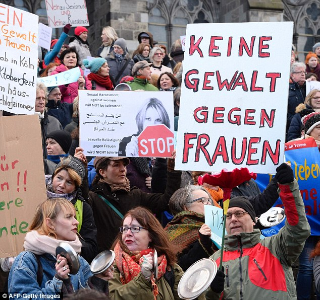 Germany is to toughen its rape laws in the wake of the Cologne New Year sex attacks carried out by migrant mobs. A man holds up a 'No violence against women' sign in Cologne during a demonstration last year