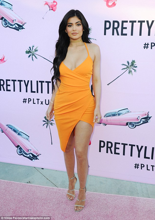 All eyes on her: Kylie Jenner made a bold statement in a tangerine frock at the US launch for clothing retailer PrettyLittleThing