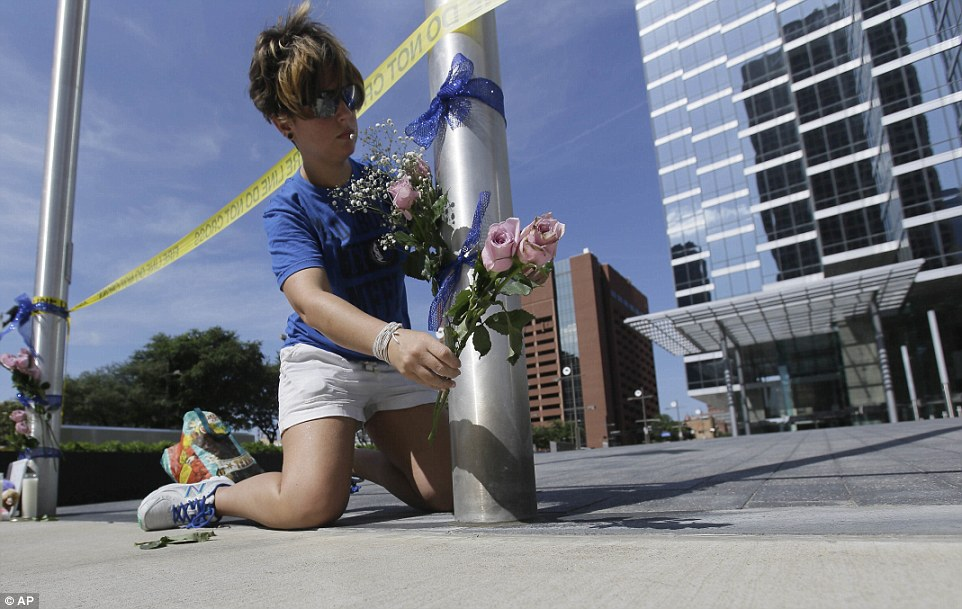 Noelle Hendrix places flowers near the scene of a shooting in downtown Dallas, Friday, July 8, 2016. Snipers opened fire on police officers in the heart of Dallas during protests over two recent fatal police shootings of black men