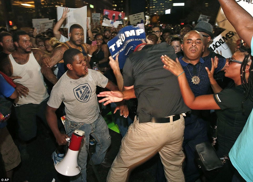 Black Lives Matter protesters have been sprayed with tear gas in Phoenix after a march against police brutality spiraled out of control. Pictured, a white man holding a Donald Trump 'Make America Great Again' placard interrupting the protest on Friday night