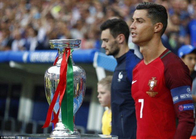 Focused: Portugal's Cristiano Ronaldo (front) and France's goalkeeper Hugo Lloris stand next to the Euro 2016 trophy before the match