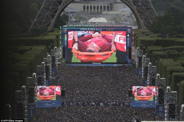 People watch on a giant screen at the fan zone of the Champs de Mars near the Eiffel tower in Paris as Ronaldo is taken off on a stretcher