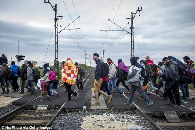 Route: Hungary is a part of the 'Balkans route' that tens of thousands of refugees and migrants are using to reach Europe. Pictured, people passing through Hungary into Austria