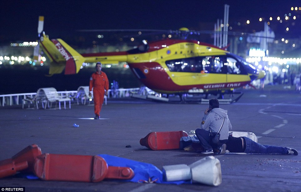 An air ambulance arrived at the scene, pictured,  to take survivors of tonight's attack to hospital