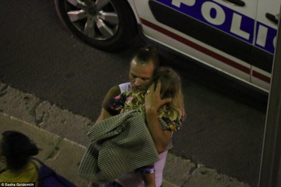 A man holding a small girl carried the traumatised youngster away from the scene of the massacre in Nice, southern France
