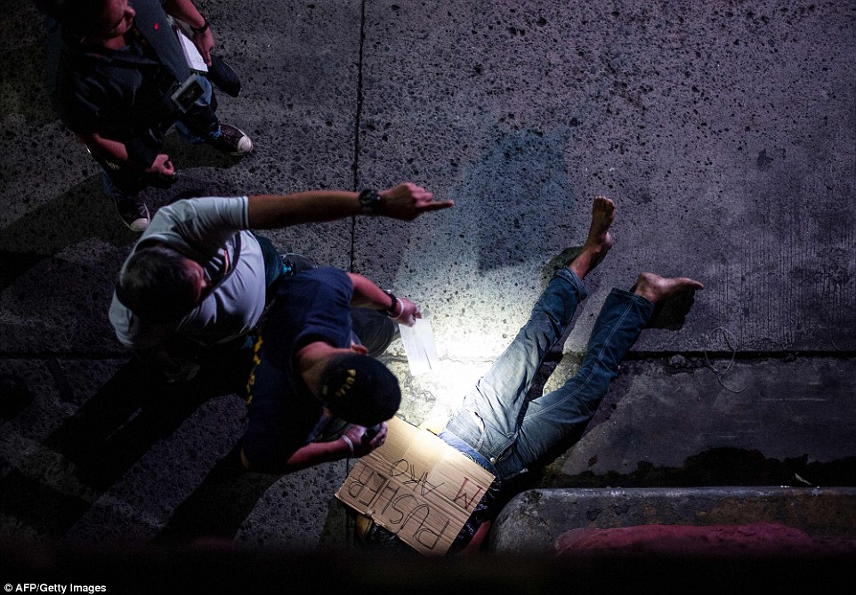 Police officers investigate the body of an alleged drug dealer, his face covered with packing tape and a placard reading 'I'm a pusher', on a street in Manila