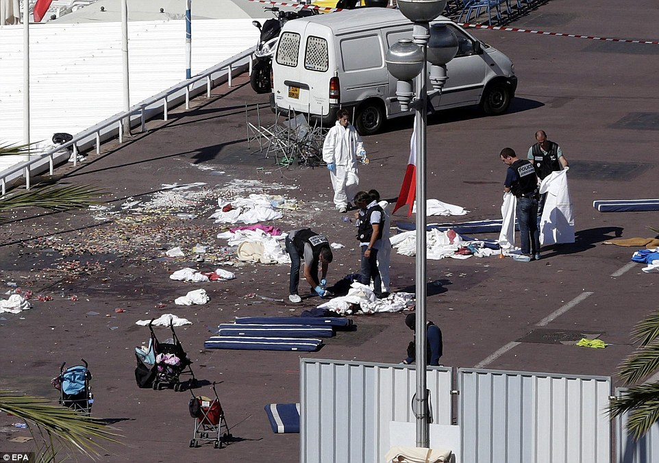 Horrifying: Police and forensics teams inspect bodies in the French sunshine where at least ten died and 50 injured - many of them in buggies left abandoned today
