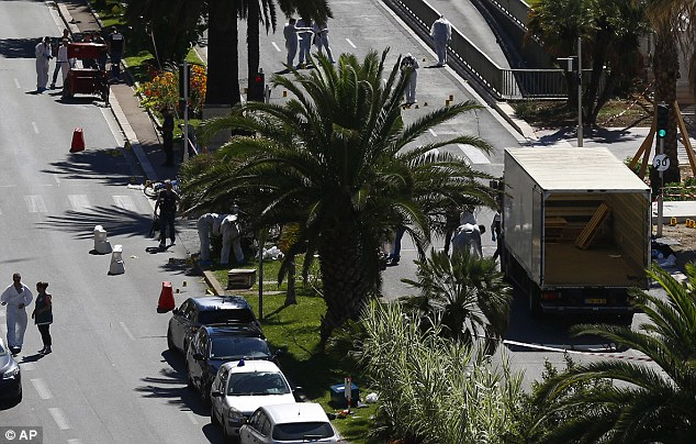 Crime scene: The lorry used as a murder weapon remains on the French Riviera city's famed waterfront promenade with police gathering evidence and marking put bullet casings with yellow numbered signs