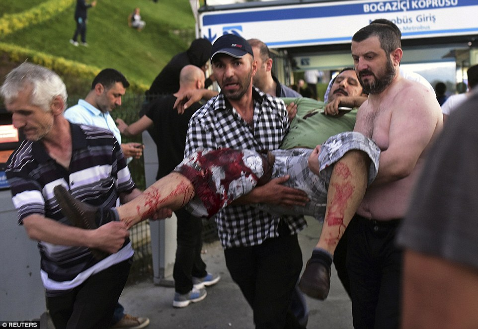 A wounded man is carried away during the attempted coup - one of hundreds injured during the blasts and gunfire battles between rebel soldiers and those loyal to Erdogan