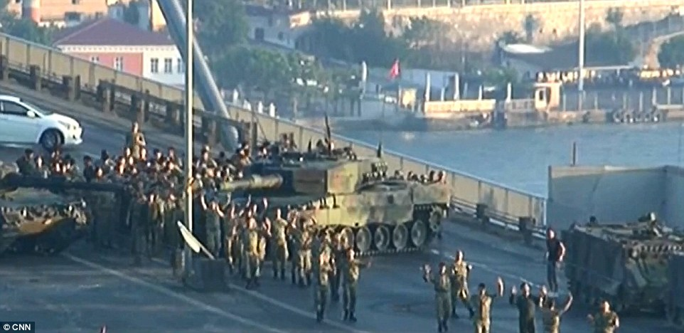 More than 750 rebels have been detained after their failed military coup that killed at least 60 as Turkish President Erdogan vows revenge for the bloody uprising (pictured: Up to 100 rebel soldiers surrendered on Bosphorus Bridge after their failed uprising)