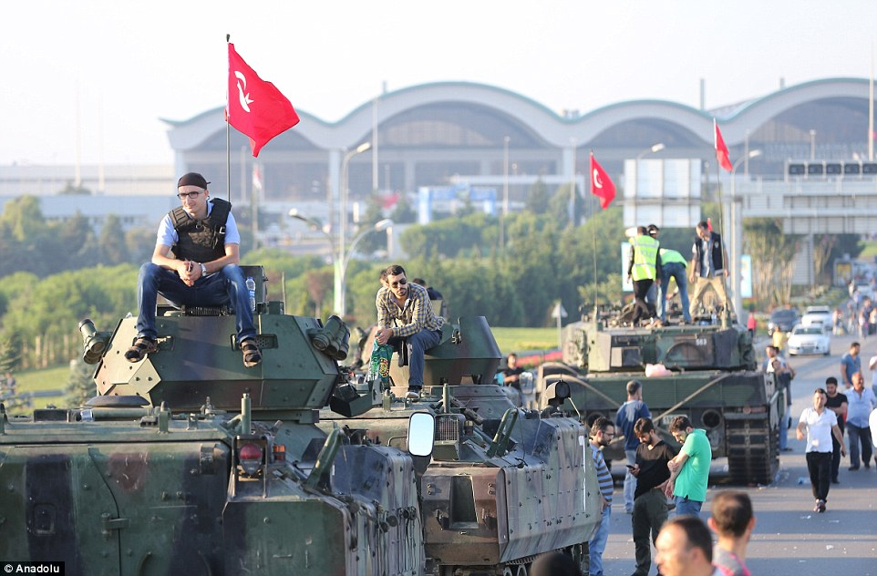 People climbs on top of the military's tanks after a group of soldiers involved in the coup attempt were neutralized by police