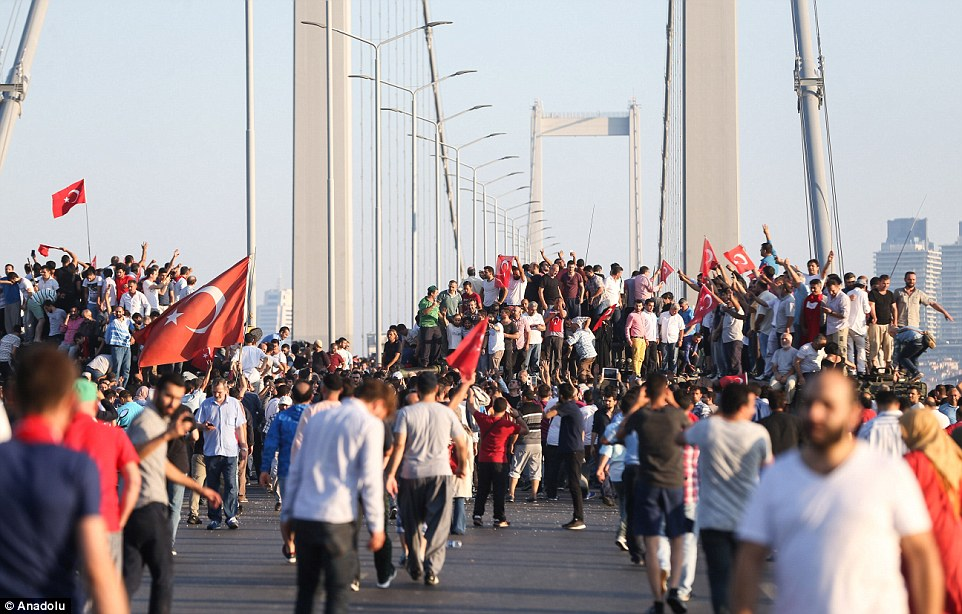 People climb on tanks after around a hundred soldiers occupying Bosphorus Bridge surrendered in Istanbul, Turkey on July 16