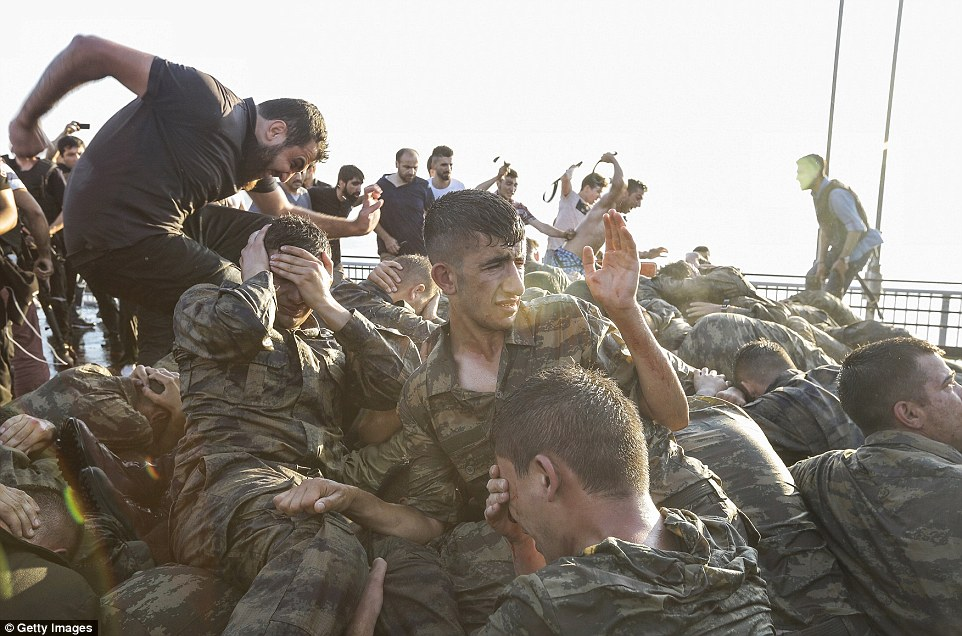 More than 2,800 rebels have been detained after their failed military coup that killed at least 250 as Turkish President Erdogan vows revenge for the bloody uprising (pictured: Up to 100 rebel soldiers surrendered on Bosphorus Bridge after their failed uprising)