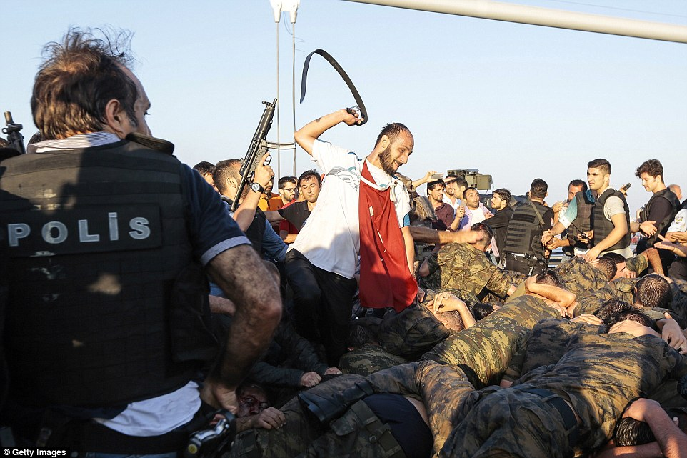 A Turkish civilian whips soldiers with his belt after they surrendered to police on Bosphorus Bridge, a strategic landmark which was seized by the army during the coup