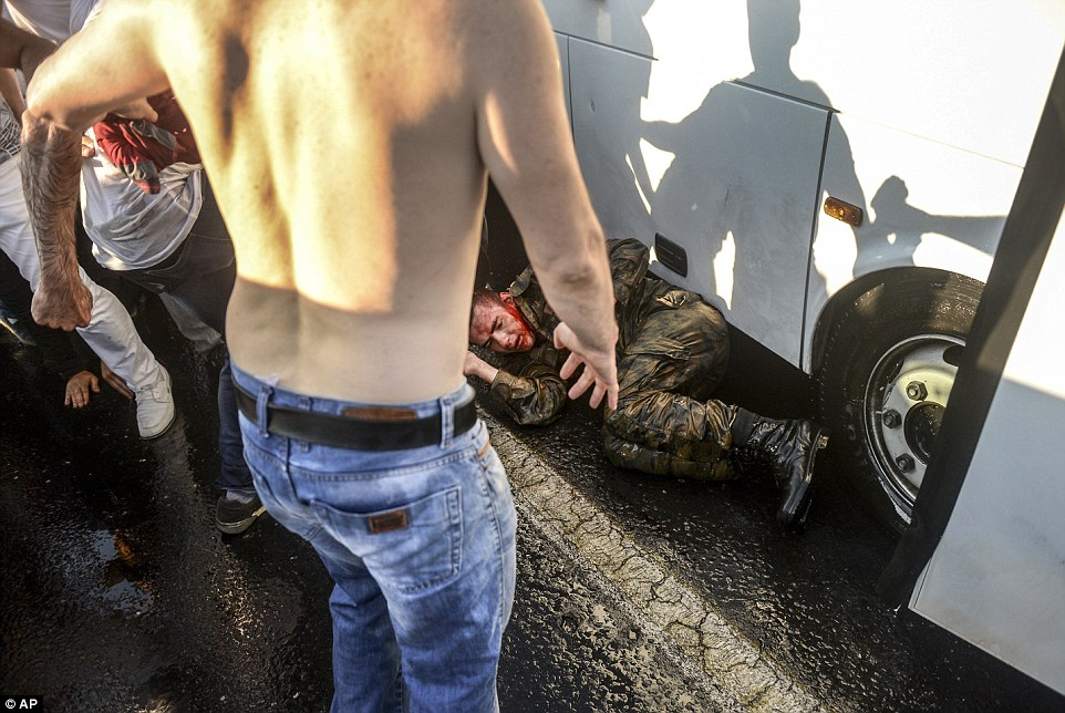 One bloodied soldier cowered underneath a coach as a mob started beating him on Istanbul's Bosphorus Bridge