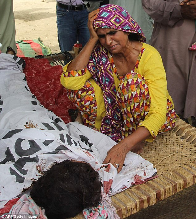 Her mother, pictured, looked inconsolable as she cried at Miss Baloch's funeral in Pakistan today