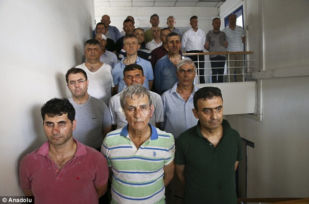 The full group, totalling 27 men, then were forced to stand on a staircase with their hands bound as they were paraded for the cameras