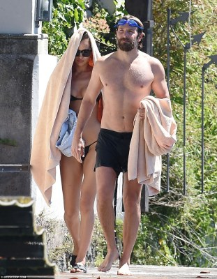 The long and short of it: Irina was seen carrying her skimpy denim shorts as she and Bradley prepared to press on with their leisurely day
