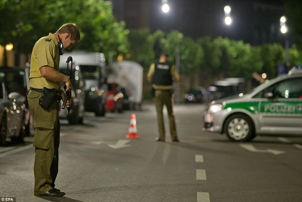 A policeman with a machine gun stands guard near the scene of the attack which has left around a dozen injured and one dead