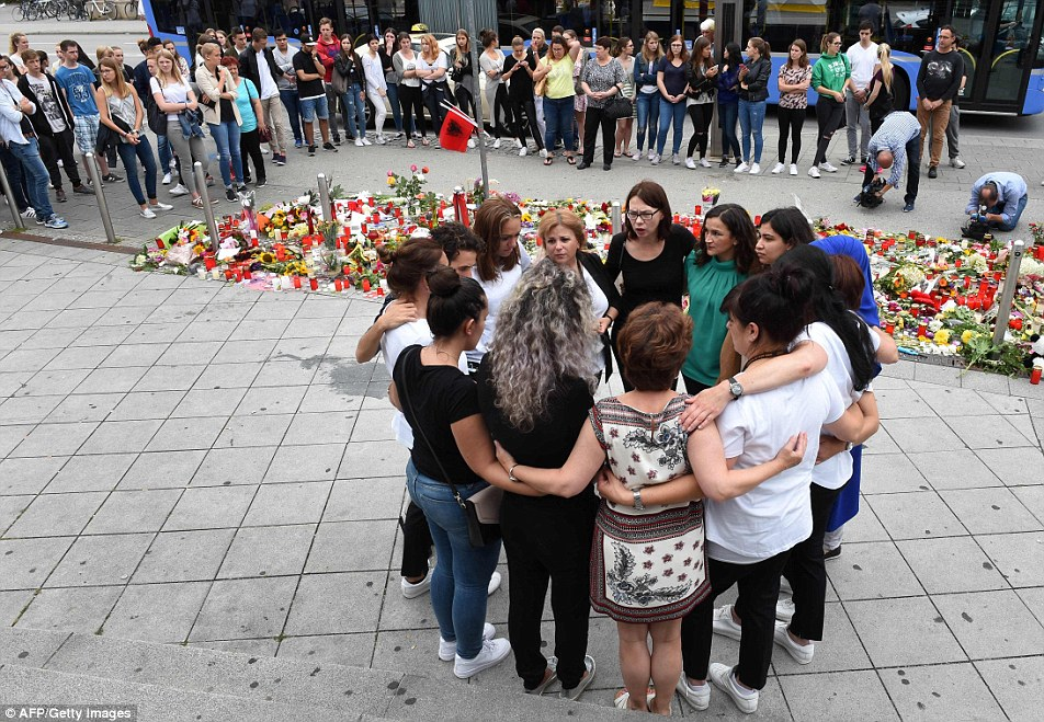 People mourn in front of candles and flowers near the Olympia shopping mall in Munich, southern Germany, where an 18-year-old German-Iranian student ran amok on a shooting spree on July 22