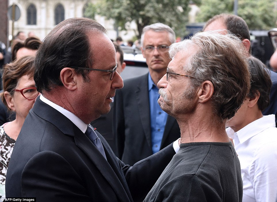 French president Francois Hollande (pictured embracing the town's mayor Hubert Wulfranc) said France is 'at war' with ISIS while the terror group has claimed responsibility for the killing