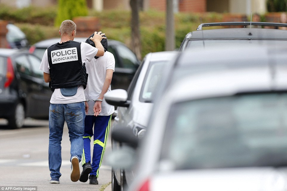 A French policeman arrests a man following a search in a house in the Normandy city of Saint-Etienne-du-Rouvra. It came after a priest was butchered at a church in the town