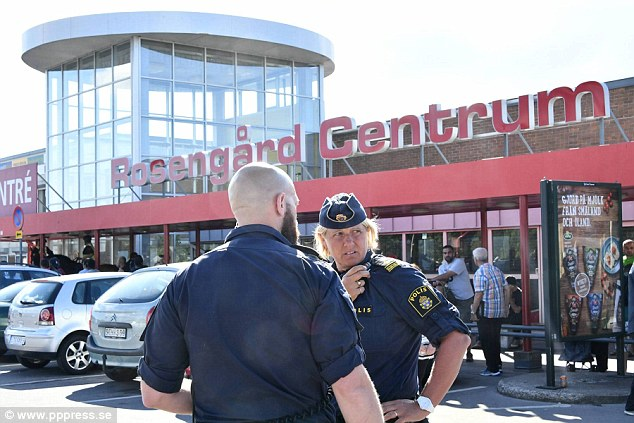 Police stand guard outside the shopping centre in Malmo, Sweden, where a man was shot in the leg on Tuesday