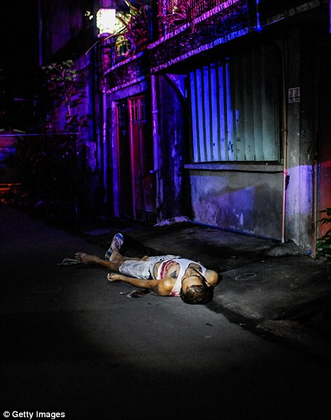 Another body is seen in an alleyway shot dead in a summary execution in Manila on July 12