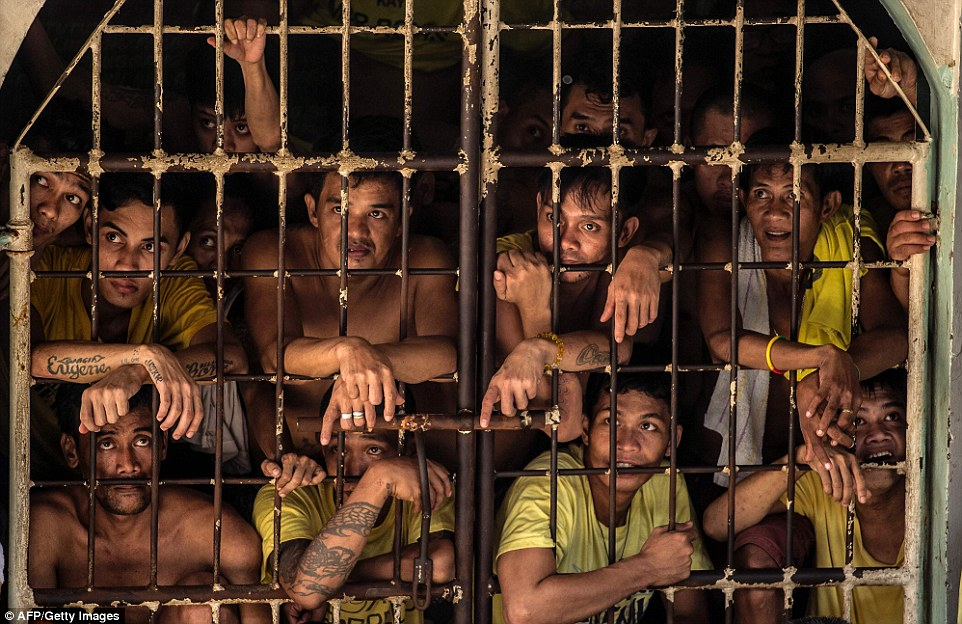 With their arms draped over the bars of their cell, a group of inmates keep a steady gaze on something happening out of sight