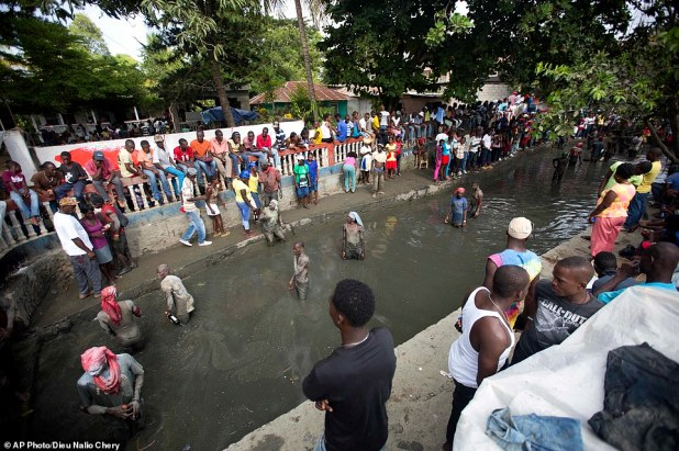 Pilgrims wade in a sacred mud pool as they attend a Voodoo ceremony which people bring flowers, rum, candles, meat and throw them into the mud as offerings