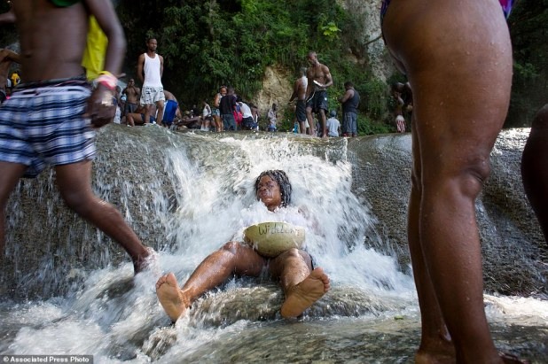 A woman holds a bowl that has her name written on it, as she bathes in a waterfall believed to have purifying powers