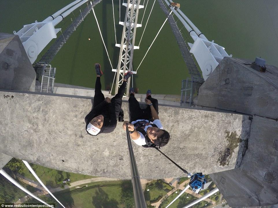 Two thrillseekers will be shown getting this selfie high above the Seri Saujana Bridge, Kuala Lumpur, Malaysia