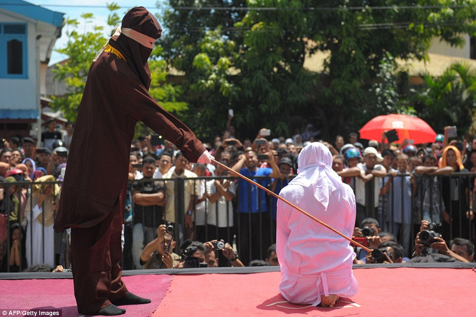 A religious officer canes an Acehnese youth onstage as punishment for dating outside of marriage, which is against sharia law