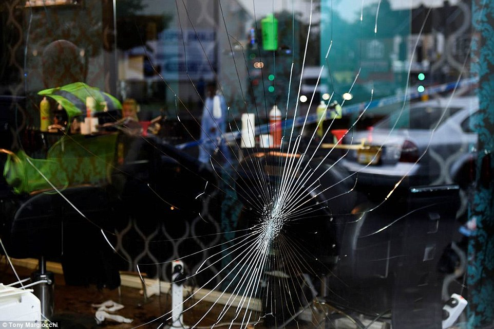 The men smashed the window of the shop (pictured), damaged one of the staff member's cars and blood could be seen splattered on the floor tiles after the brutal attack
