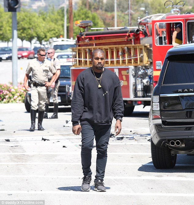 Rattled: Rapper Kanye looked concerned as he arrived on the scene, along with fire crews and paramedics