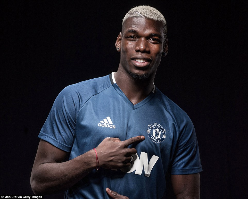 Pogba points to the United badge as he completed his homecoming in the summer's biggest transfer deal