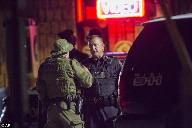 Police confer outside of a house in Strathroy, Ontario, where an operation continued well into Wednesday night