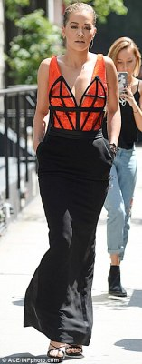 Vibrant:Rita headed to work in a tight-fitting dress formed of a black figure-hugging maxi skirt and a vibrant orange top