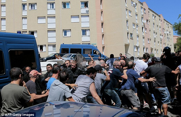Pictured, protesters clash with riot police as locals vent their anger over the burkini row