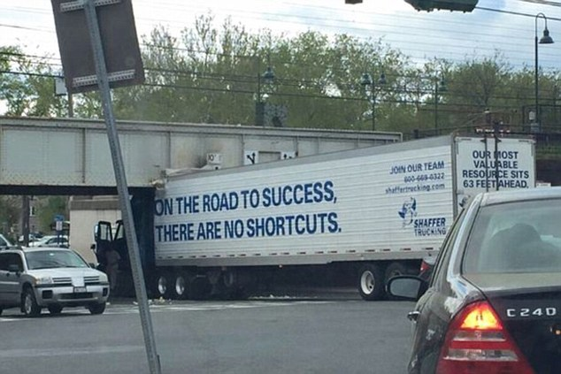 A tall lorry which has seemingly taken a gamble on a low bridge and crashed spectacularly, branded with the slogan, 'on the road to success, there are no shortcuts'
