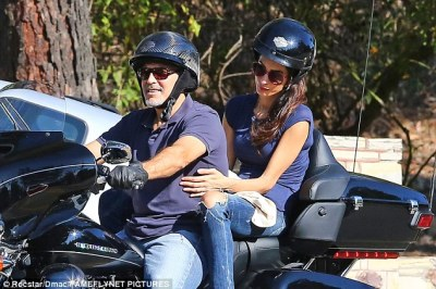 Loving touch: Amal lovingly held on to her husband for their spin around town