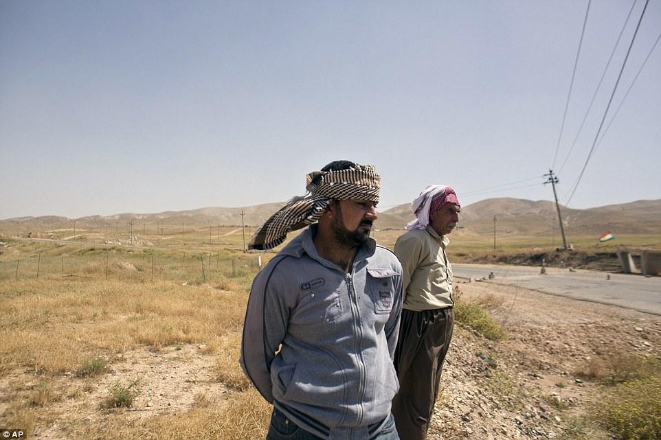 Arkan Qassim (centro) se sitúa en el sitio donde fue testigo de la muerte de los hombres de Yazidi incluyendo dos hijos de Rasho Qassim (derecha), en agosto de 2014 en el norte de Irak, Hardan docenas.  Los dos sobrevivientes dicen que simplemente quieren exhumaron las tumbas
