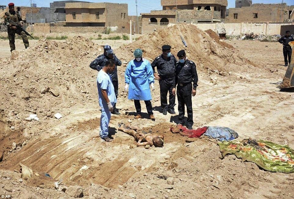 Un equipo forense fuerzas de seguridad iraquíes trabaja en el sitio de una fosa común que se cree contiene los cuerpos de civiles iraquíes, fuerzas de seguridad y miembros de sus familias, incluyendo mujeres y niños, muertos por ISIS en la zona del estadio en Ramadi, Irak
