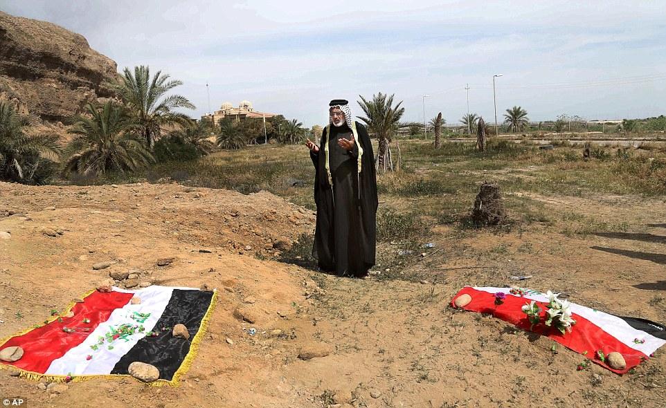 Un iraquí ora por su pariente muerto en el sitio de una fosa común que se cree contiene los cuerpos de los soldados iraquíes muertos por ISIS cuando invadieron el campo Speicher base militar en Tikrit, Irak.  Muchas de las mismas tumbas son bastante fácil de encontrar, la mayor parte cubierto con sólo una fina capa de tierra